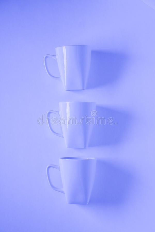 3 blue coffee mugs on blue background in a vertical row with empty copyspace. 3 monochromatic blue coffee mugs lined up in a row on blue background with blank royalty free stock photography