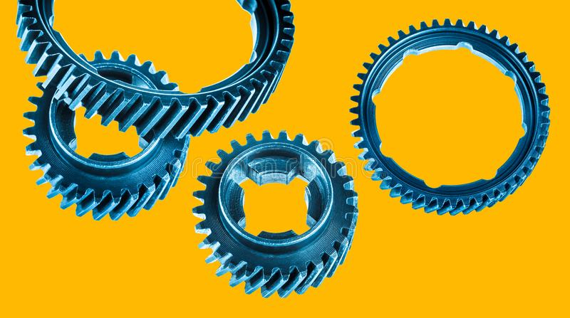 Group of different gearwheels. Blue cogwheels isolated on yellow background royalty free stock photos