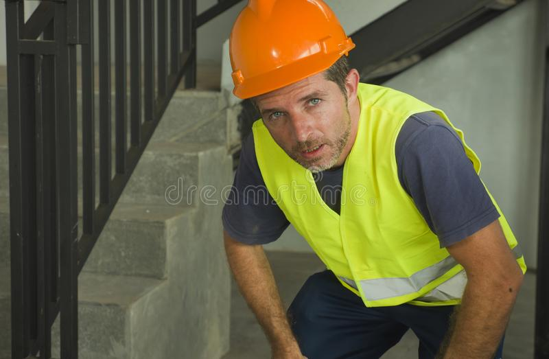 Blue collar job lifestyle. Portrait of tired and exhausted construction worker in helmet and vest at building site taking a breath stock photography