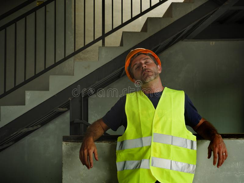 Blue collar job lifestyle. Portrait of young attractive and exhausted construction worker in helmet and vest at building site royalty free stock image