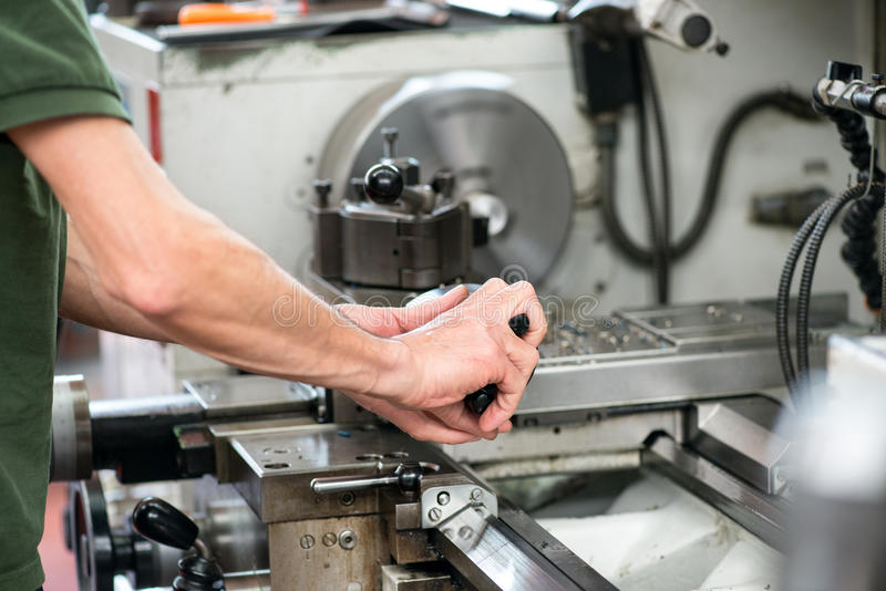 Blue collar or skilled labor working on a lathe. Blue collar or skilled workman working on a large industrial lathe guiding a component with his hands during royalty free stock photography