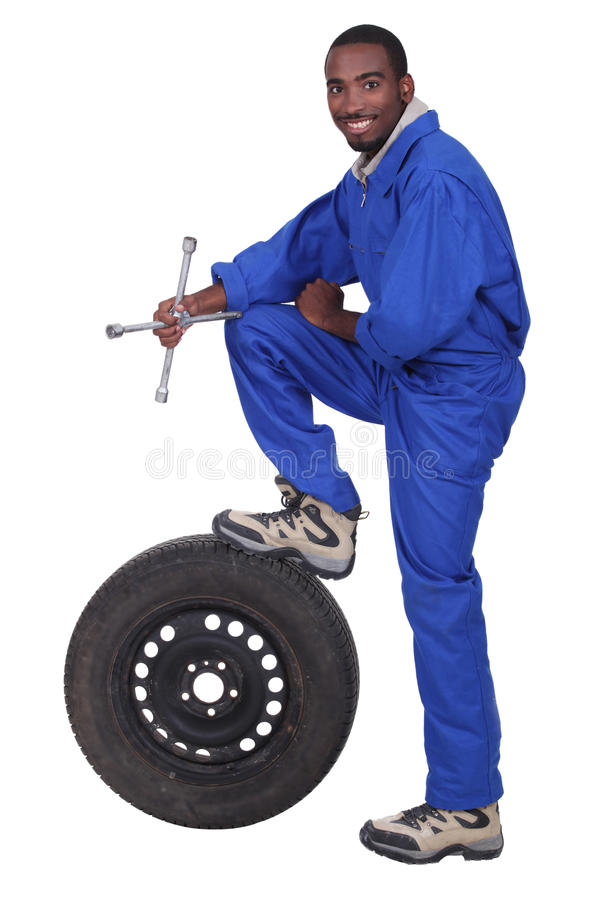 Blue collar worker. Blue collar holding cross faucet with leg resting on pneumatic tyre royalty free stock images