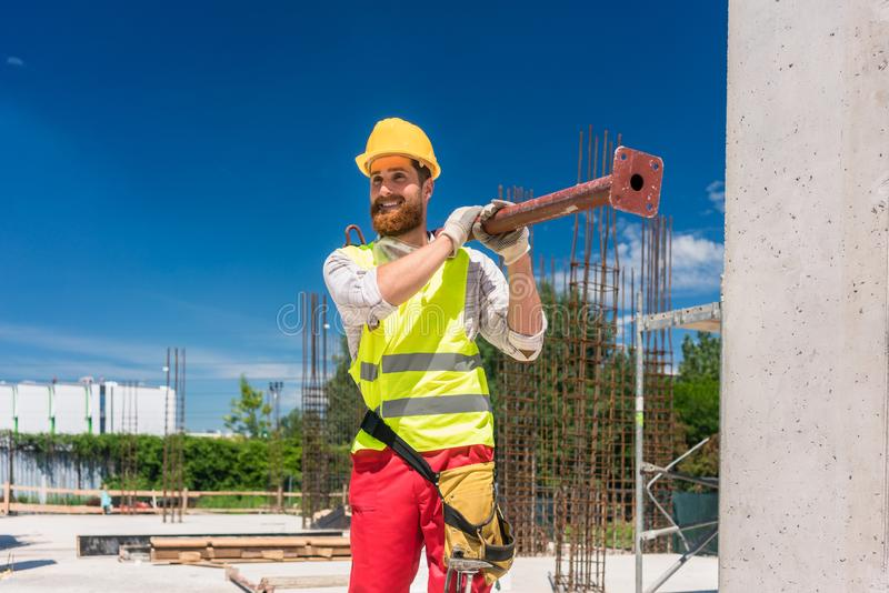 Blue-collar worker carrying a heavy metallic bar during work royalty free stock photography
