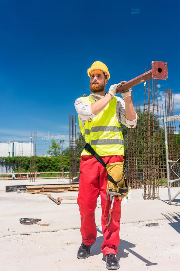 Blue-collar worker carrying a heavy metallic bar during work royalty free stock image