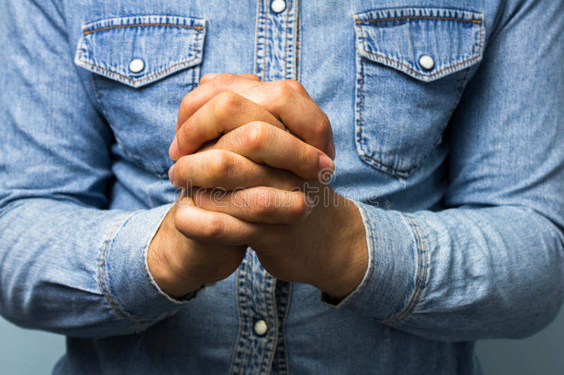 Blue collar worker with hands folded. In prayer stock photo