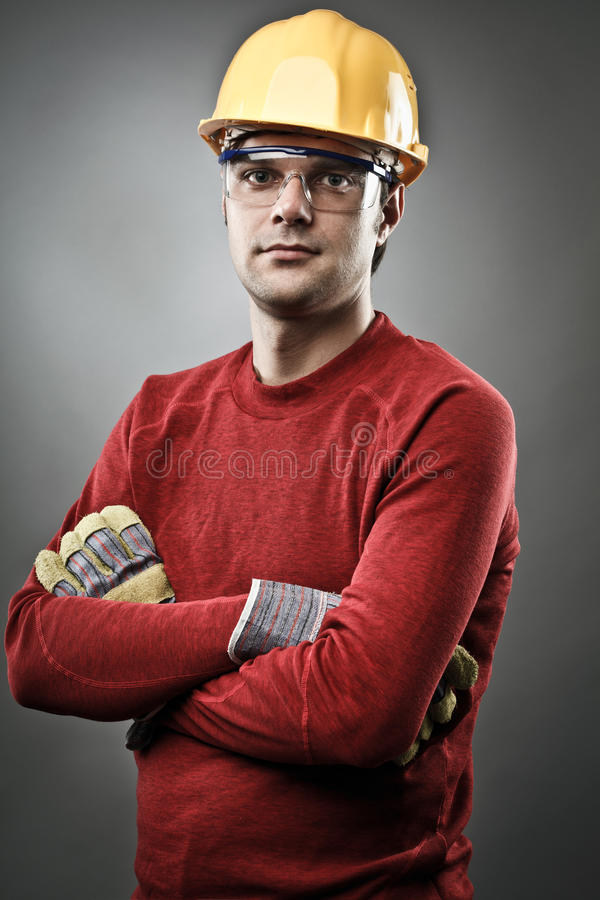 Blue collar worker with hardhat. Young blue collar worker with yellow protective helmet and gloves stock image