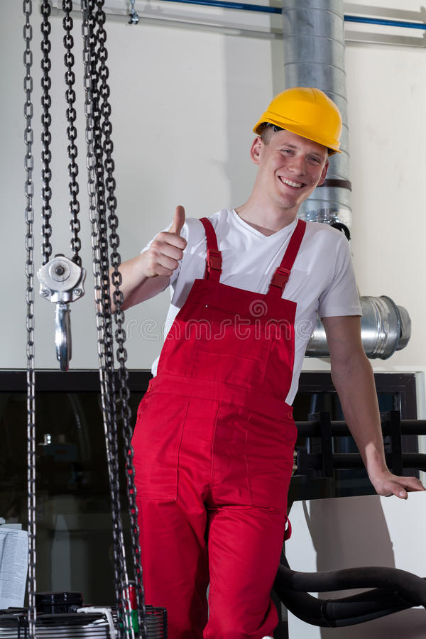 Blue-collar worker showing thumbs up sign. Blue-collar worker standing near to lifting equipment and showing thumbs up sign stock photos