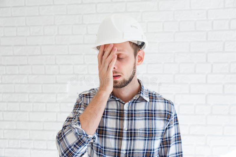 A blue collar worker wearing a hardhat is covering his face with his hand stock images