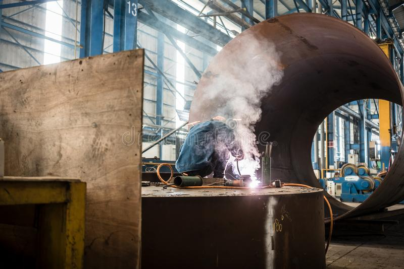 Blue-collar worker welding in the interior of a factory royalty free stock photography