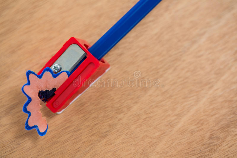 Blue color pencil being sharpened on wooden background stock images