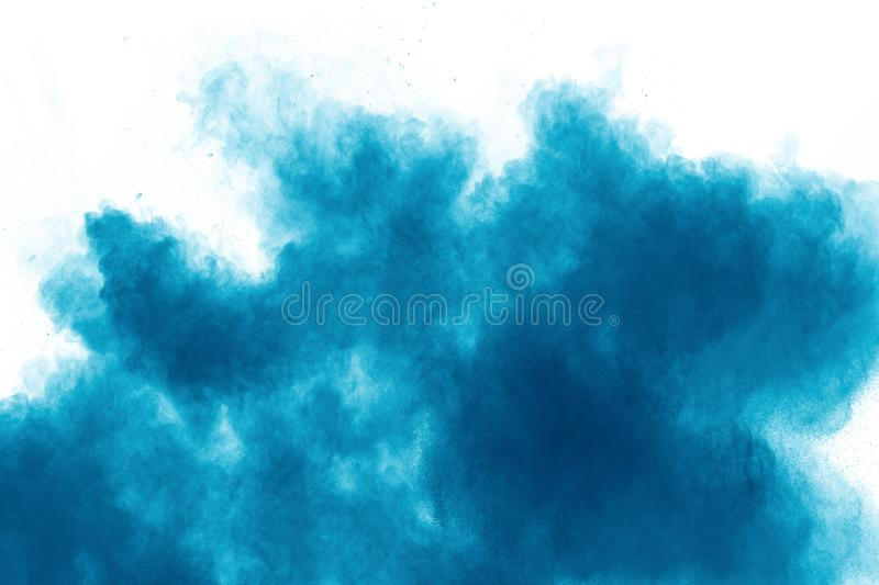 Blue color powder explosion cloud on white background.Closeup of Blue dust particles splash on background royalty free stock photo