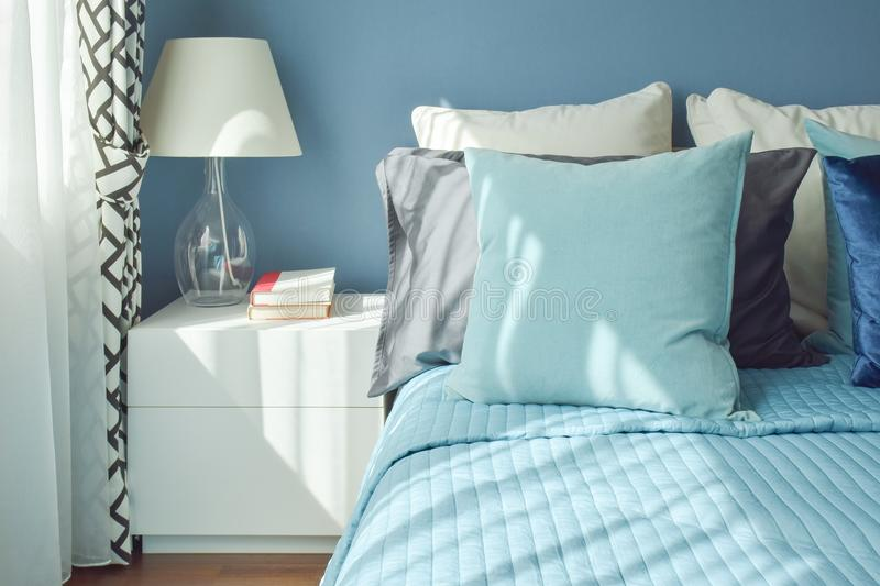 Blue color scheme bedding and white table lamp with natural light royalty free stock image