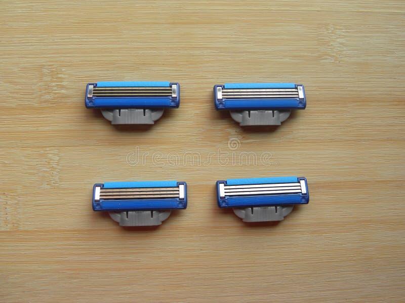 Razor blade cartridges. 4 blue color shaving razor blade cartridges kept on wooden table royalty free stock photos