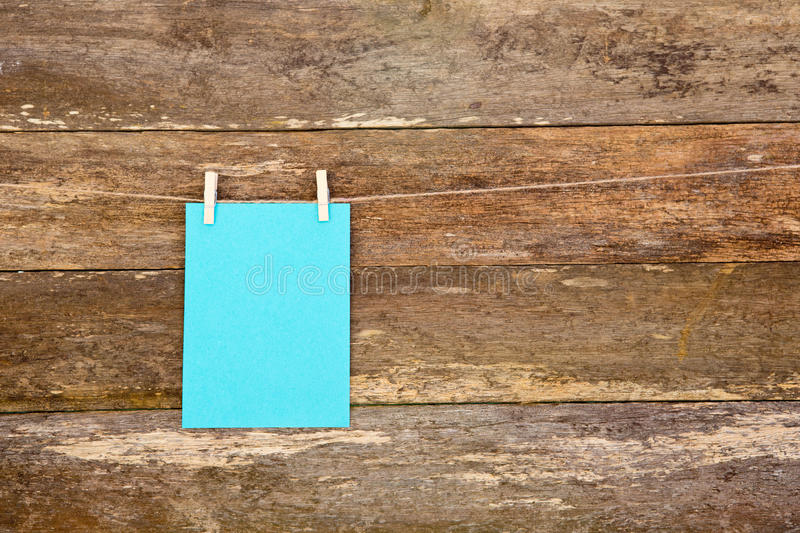 Blue colored paper - cardboard on clothespins hanging againts old timber plank background. Blue colored paper - cardboard on clothespins hanging againts old stock image