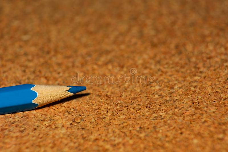 Blue colored pencil on cork boards is close-up, soft focus royalty free stock photography