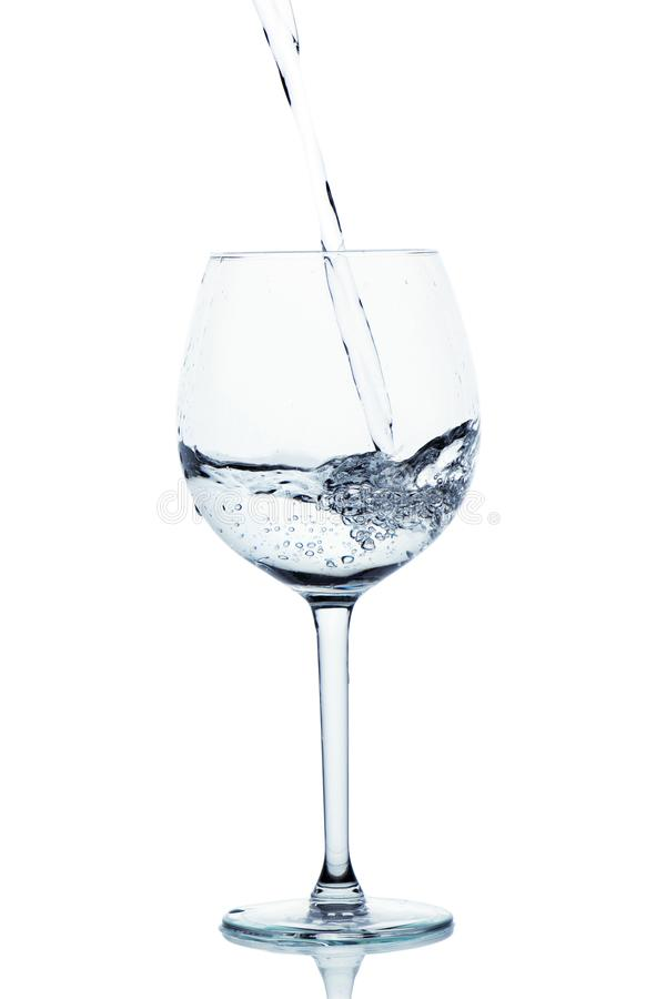 Blue colored water is pouring into the wine glass. stock photo