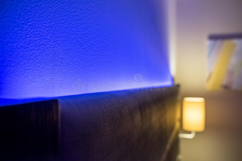 Ambient blue lighting seen illuminated behind a headboard in a luxury apartment. The blue colour creates a relaxing atmosphere for the evening. Also in view is royalty free stock photos