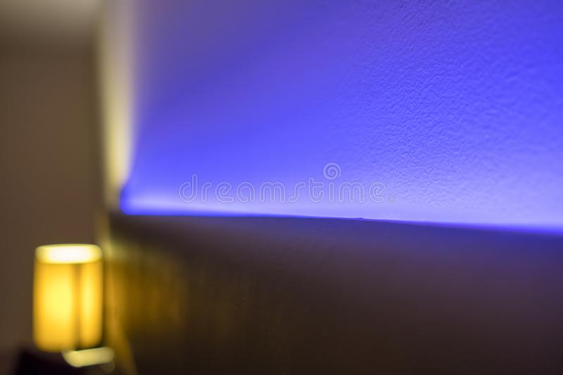 Ambient blue lighting seen illuminated behind a headboard in a luxury apartment. The blue colour creates a relaxing atmosphere for the evening. Also in view is stock photo