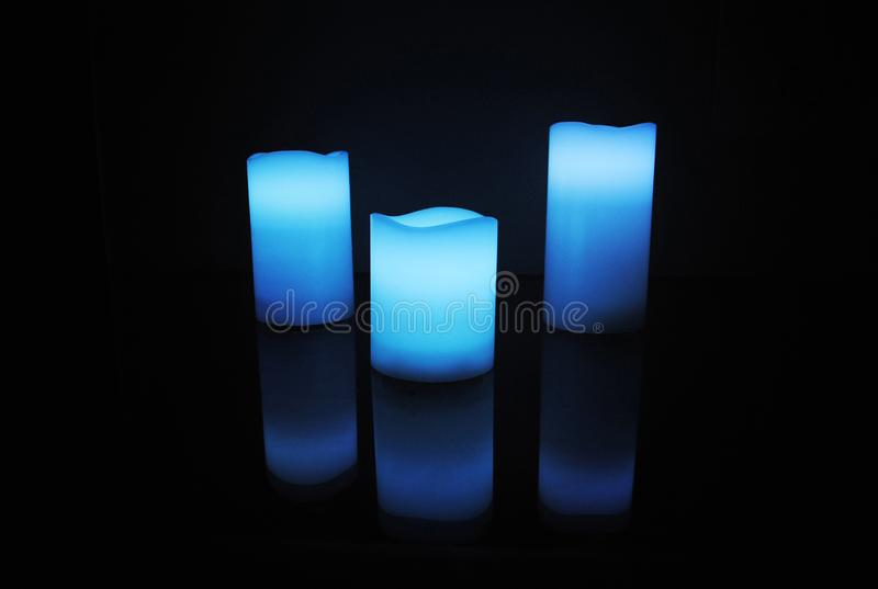 Blue colour wax scented candles with candle reflection.  stock photography