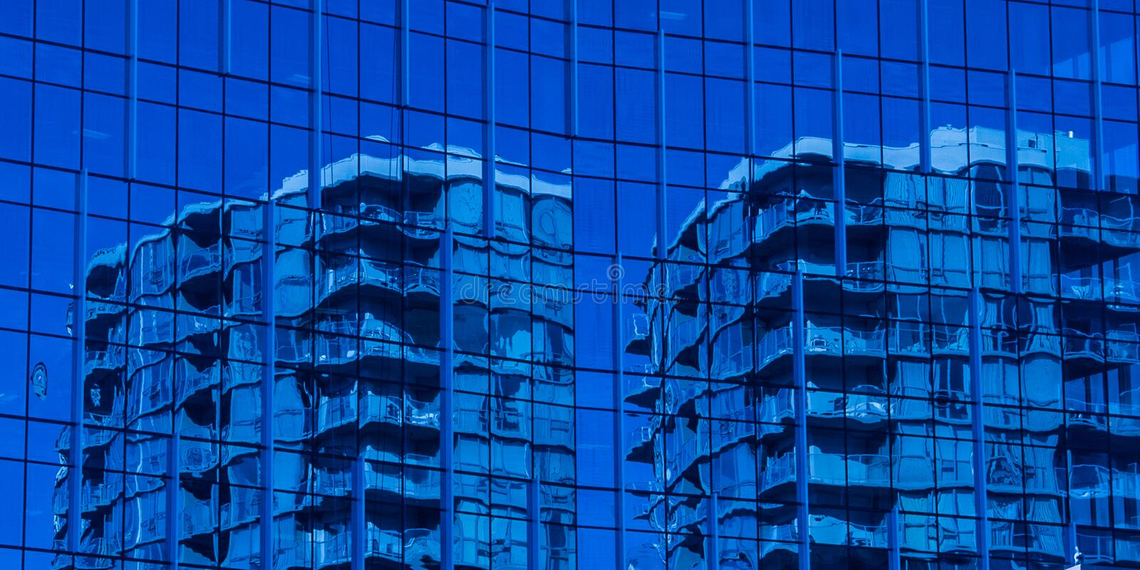 Blue coloured building reflecting off of blue glass royalty free stock photo