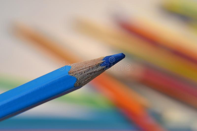 Blue coloured pencil. On colourful background royalty free stock images