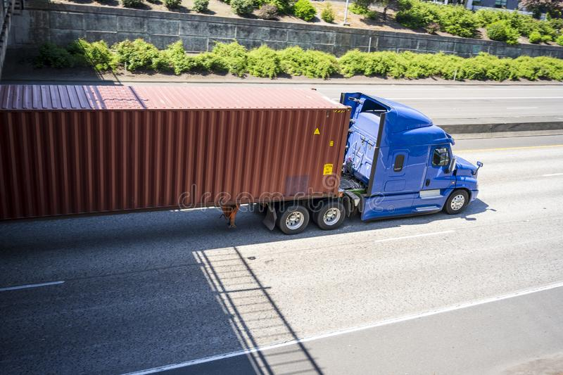 Blue comfort long haul big rig semi truck with long container driving on the divided highway road running under bridge. Blue comfort long haul professional royalty free stock photos