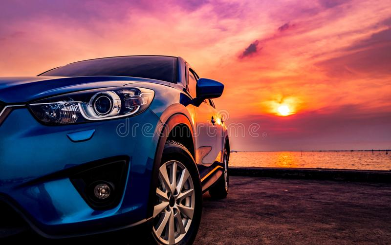 Blue compact SUV car with sport and modern design parked on concrete road by the sea at sunset. Environmentally friendly royalty free stock photography