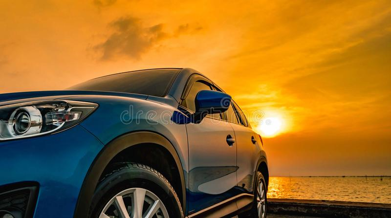 Blue compact SUV car with sport and modern design parked on concrete road by the sea at sunset. Environmentally friendly royalty free stock images
