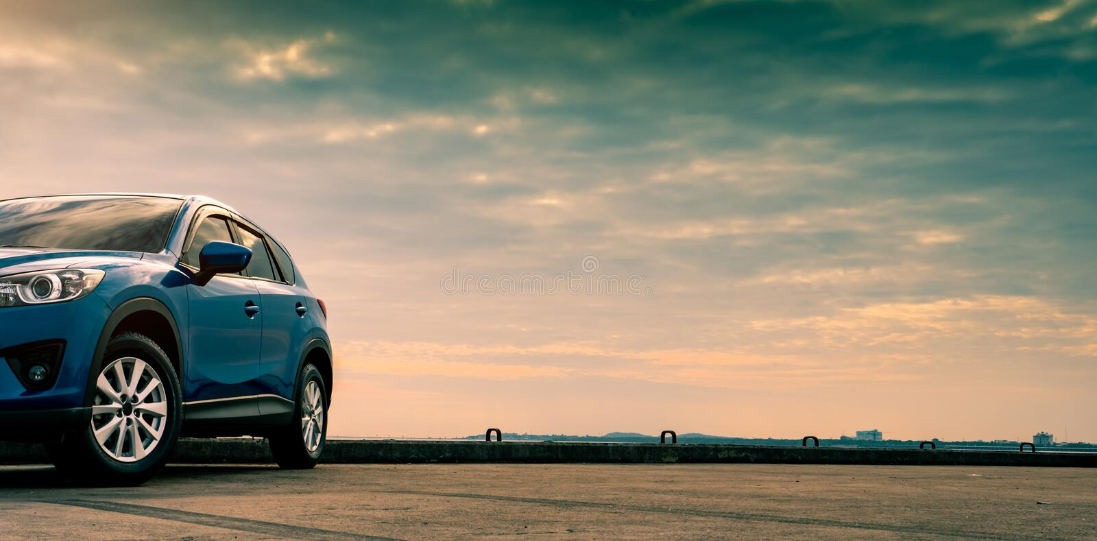 Blue compact SUV car with sport and modern design parked on concrete road by the sea. Hybrid and electric car technology concept. Car parking space. Automotive stock photos