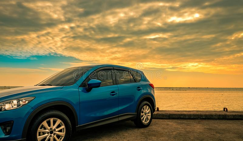 Blue compact SUV car with sport and modern design parked on concrete road by sea at sunrise. Environmentally friendly technology. stock photography