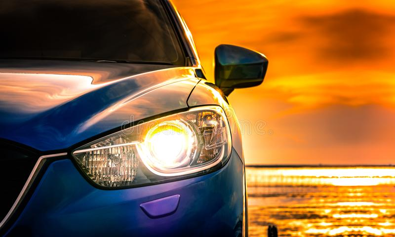 Blue compact SUV car with sport and modern design parked on concrete road by the sea at sunset. Environmentally friendly. Technology. Business success concept royalty free stock photos
