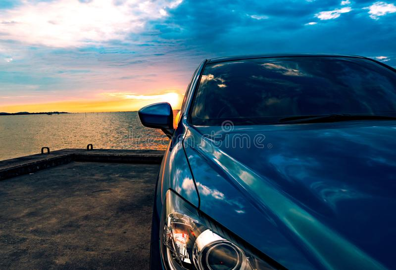 Blue compact SUV car with sport and modern design parked on concrete road by the sea at sunset. Environmentally friendly technolog. Y. Business success concept royalty free stock images