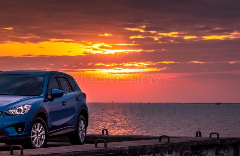 Blue compact SUV car with sport and modern design parked on concrete road by sea at sunset. Environmentally friendly technology. Hybrid and electric car stock photography