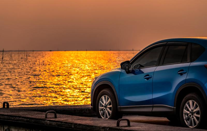 Blue compact SUV car with sport and modern design parked on concrete road by the sea at sunset. Environmentally friendly. Technology. Electric car technology stock photography