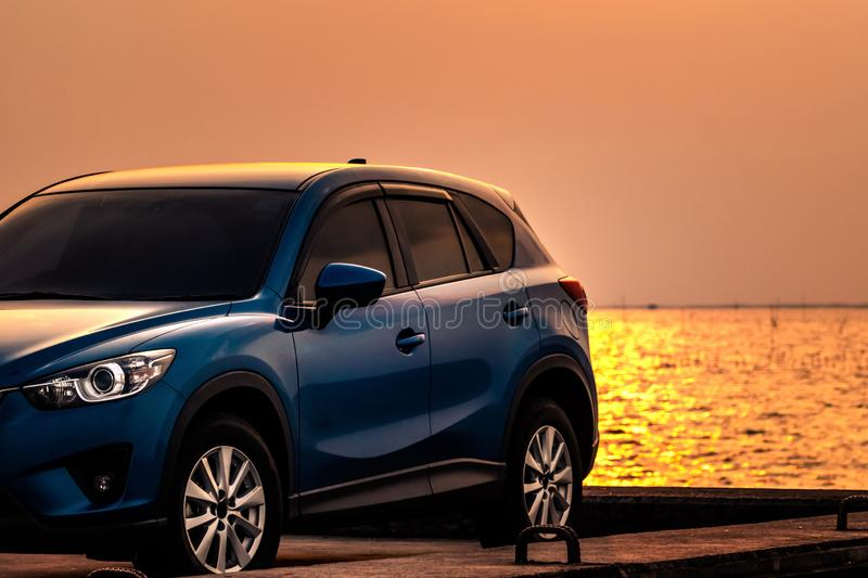 Blue compact SUV car with sport and modern design parked on concrete road by sea at sunset. Environmentally friendly technology. Hybrid and electric car royalty free stock photos