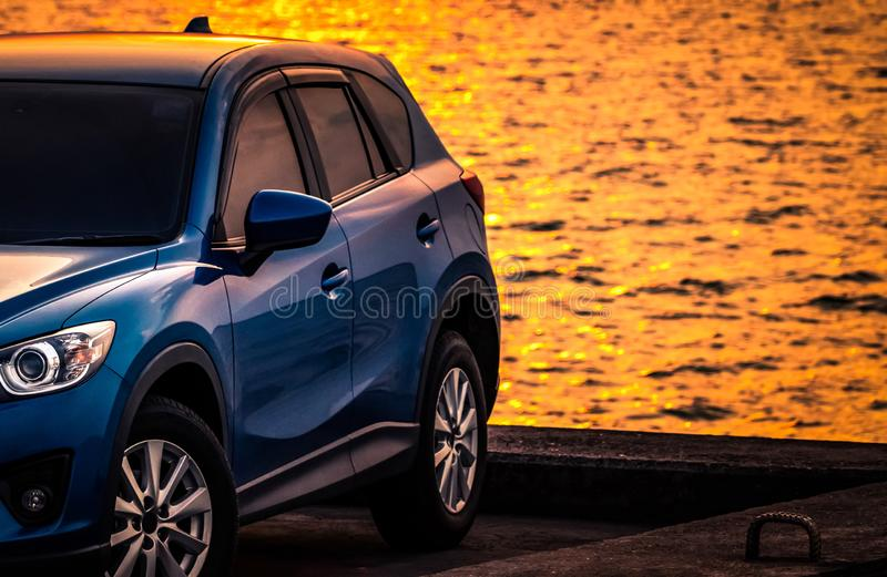Blue compact SUV car with sport and modern design parked on concrete road by sea at sunset. Environmentally friendly technology. Hybrid and electric car royalty free stock images