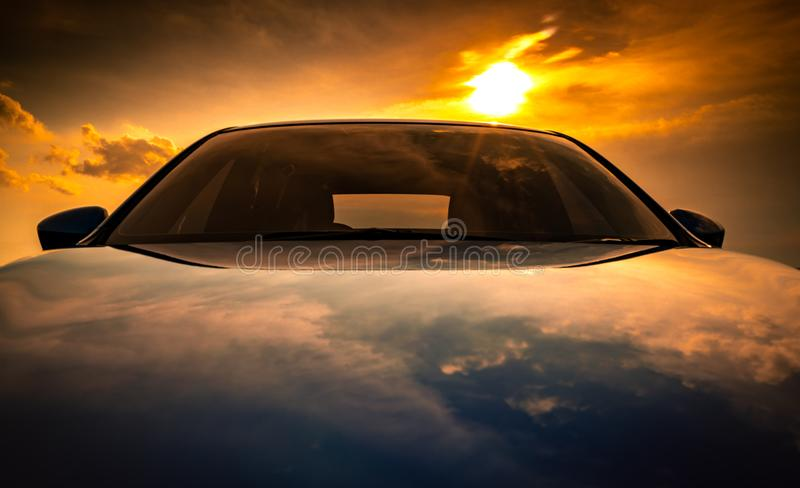 Blue compact SUV car with sport, modern, and luxury design parked on concrete road by the sea at sunset. Front view of beautiful royalty free stock photos