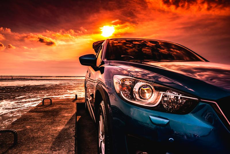 Blue compact SUV car with sport, modern, and luxury design parked on concrete road by the sea at sunset. Front view of beautiful stock photography