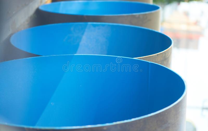 Blue construction big pipe before install with sun flare ,vertical stock photo