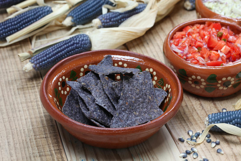 Blue corn tortilla chips. With salsa stock photos