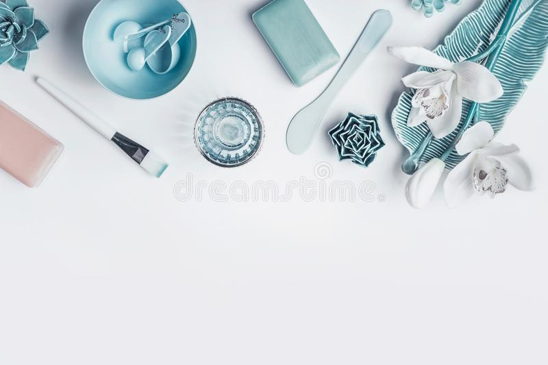 Blue Cosmetic setting for facial skin care with white orchid flowers, homemade mask tools and accessories on white background, top royalty free stock photography