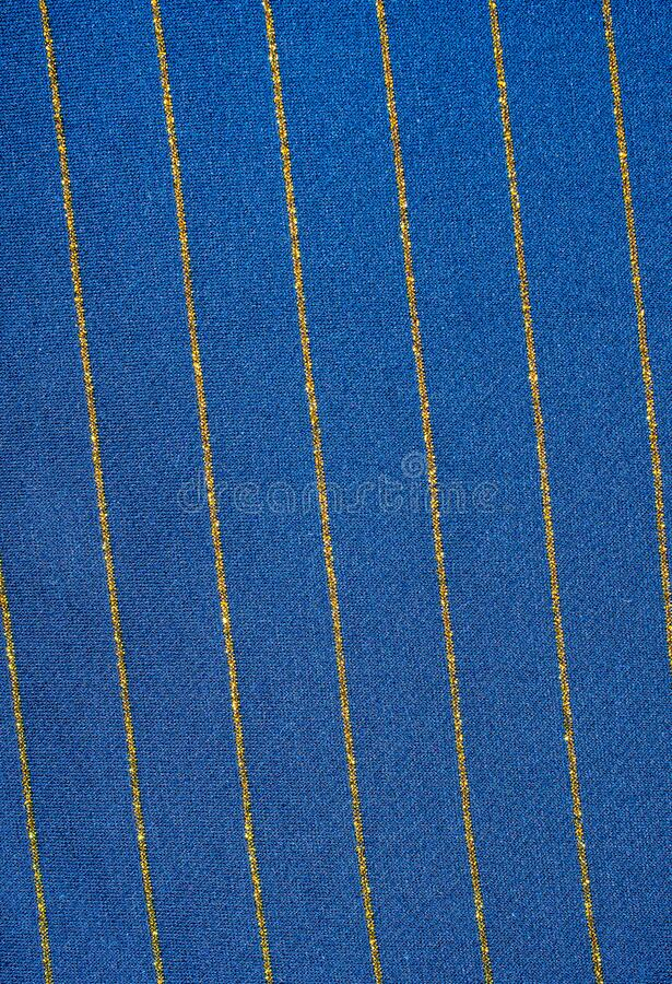 Blue cotton material with golden stripes with visible texture.  royalty free stock photo
