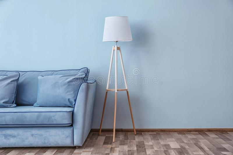 Blue couch and floor lamp near wall stock images