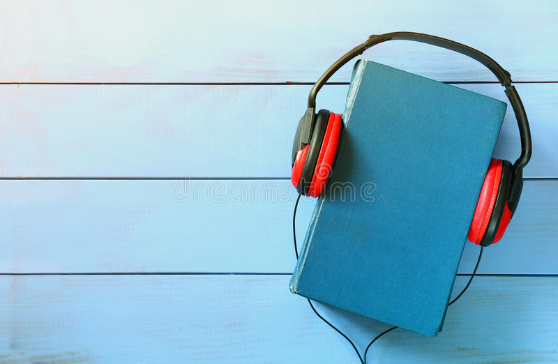 Blue cover book and headphones over wooden table royalty free stock photo