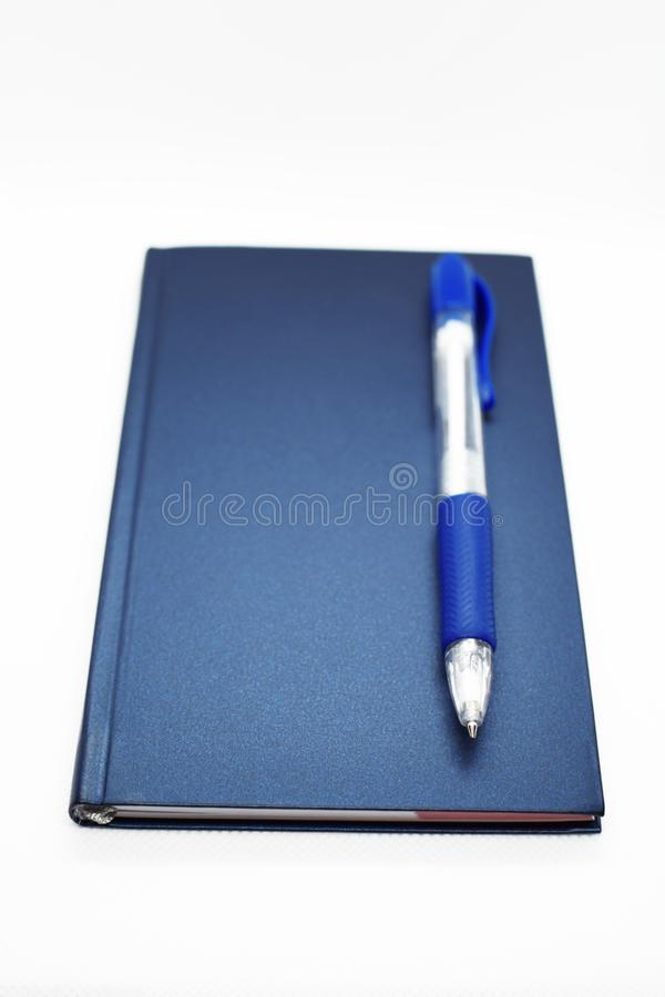 Blue cover notebook with pen stock image