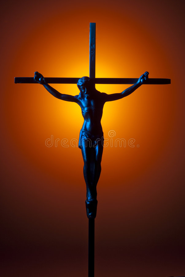 Blue crucifix. Blue lit crucifix with orange spot as background stock photography