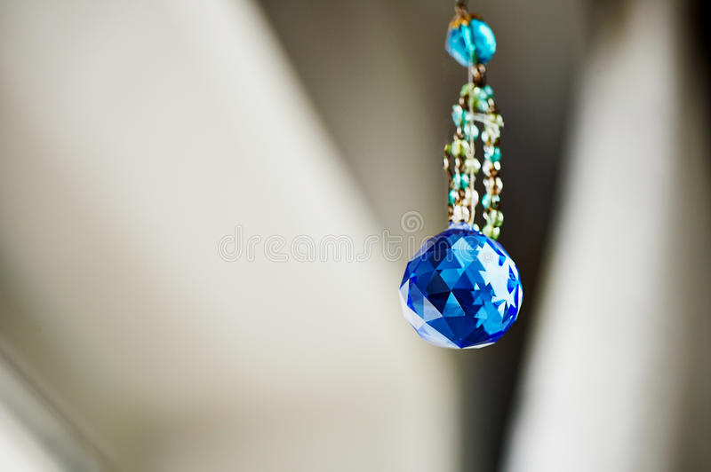 Blue crystal Feng Shui hanging on a string of beads stock photography