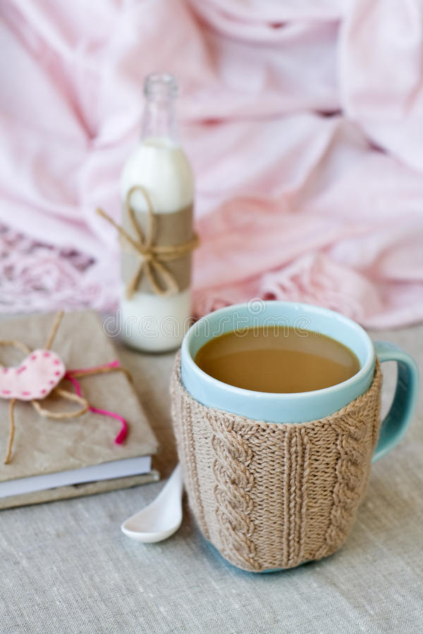Blue cup of coffee in Knitted sweater, vintage notebook. For records in a bottle with milk stock images