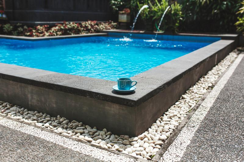 A blue cup of coffee stands on the corner of a tropical pool overlaid with white stone. Comfortable vacation in Asia stock images