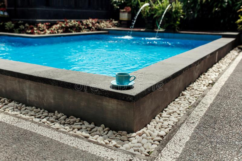 A blue cup of coffee stands on the corner of a tropical pool overlaid with white stone. Comfortable vacation in Asia.  royalty free stock image